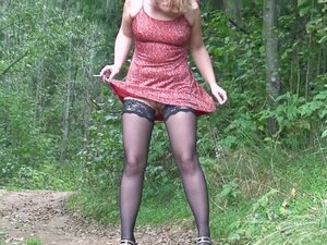 Young girl in a dress pisses outdoors