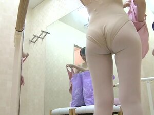 A ballet dancing girl is getting topless in the changing room