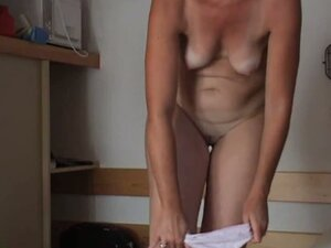 Mature woman gets dressed in the changing room in front of a well hidden camera