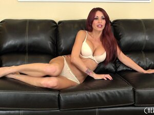 Sweet redhead Monique Alexander does some sexy posing on the couch