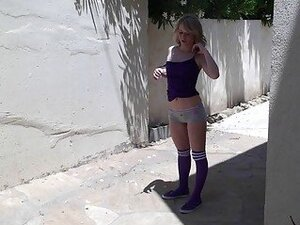 Playful blonde teen in shorts stripps and teases outdoor