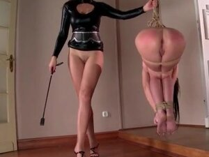She hangs from the ceiling in rope bondage