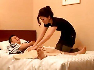 Naughty Japanese MILF gives a handjob to a guy in the bedroom