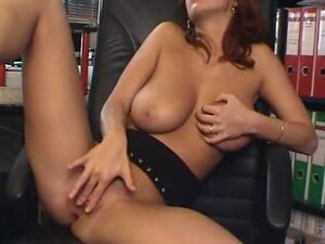 Solo redhead in office fingers her pussy