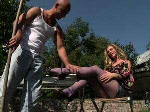 Blonde outside in pantyhose is using her feet on his throbbing bone